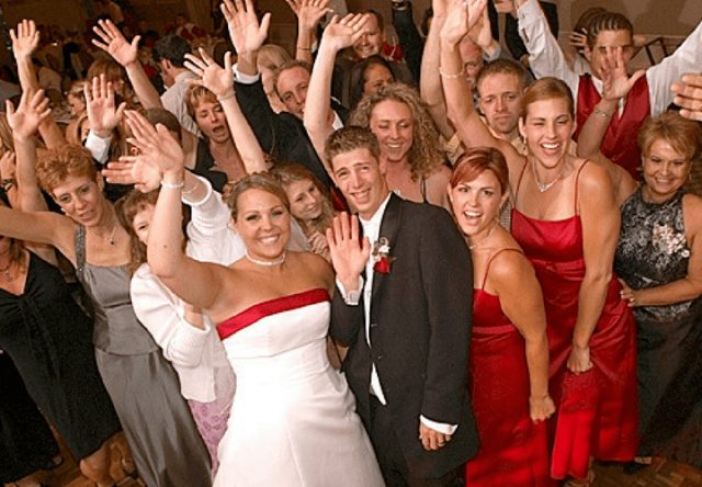 bride and groom with bridal party and friends wave
