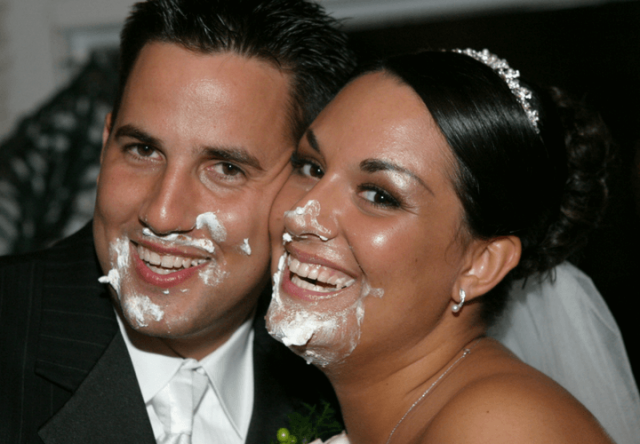 bride and groom with cake smeared on their faces