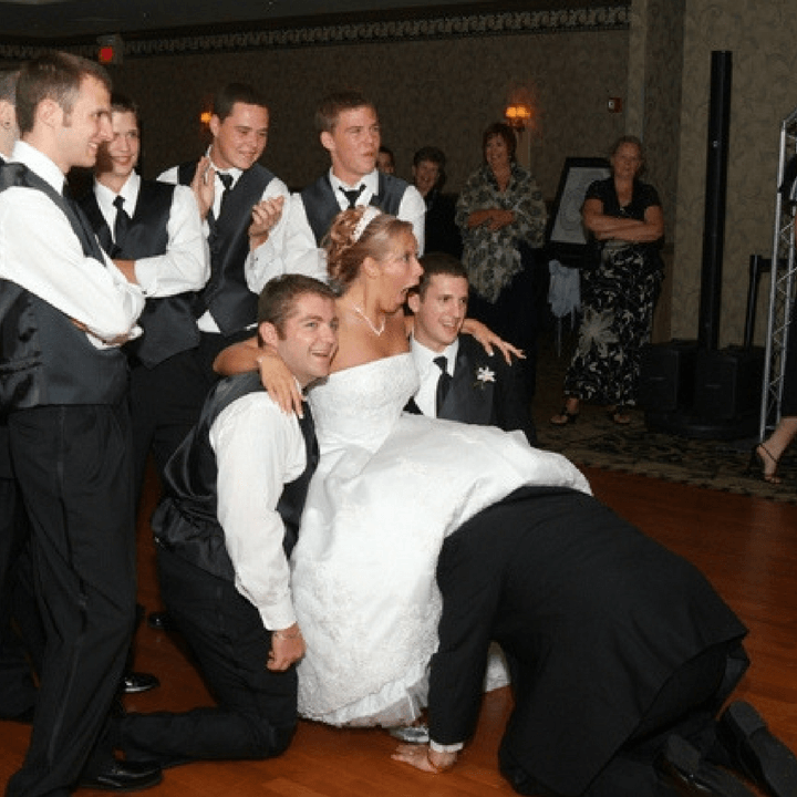 Bride and groomsmen, groom removing garter with head under bride's dress