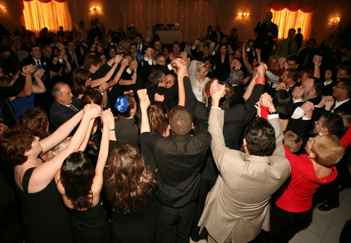 group raising their arms in celebration around the bride and groom